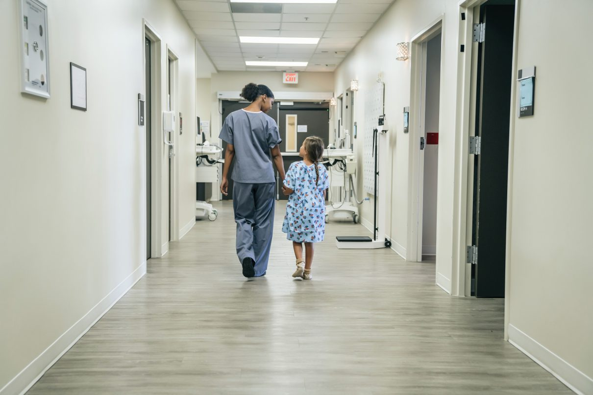 Nurse walking with girl in hospital corridor